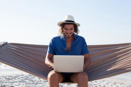 Foto de Smiling Man using laptop while sitting on hammock at beach during sunny day - Imagen libre de derechos