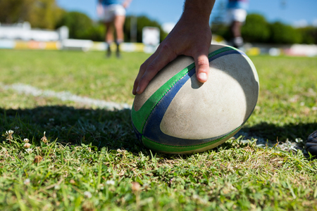 Photo pour Cropped image of player touching rugby ball at field - image libre de droit