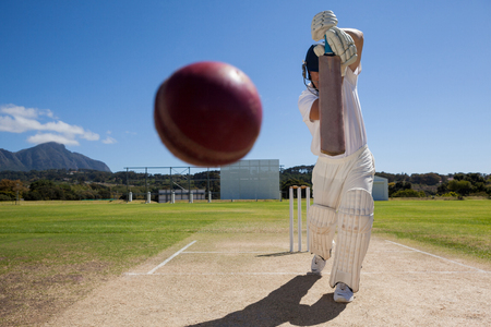 Foto de Full length of batsman playing cricket on pitch against blue sky during sunny day - Imagen libre de derechos
