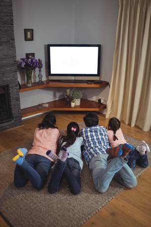Photo pour Family watching television together in living room at home - image libre de droit