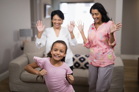 Photo for Portrait of smiling girl dancing with family at home - Royalty Free Image
