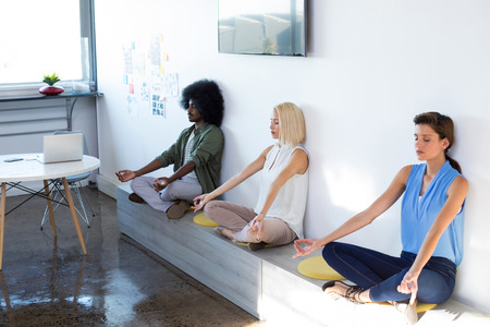 Photo pour Executives doing yoga in office - image libre de droit