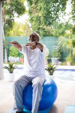 Foto de Senior man exercising while sitting on fitness ball yard - Imagen libre de derechos