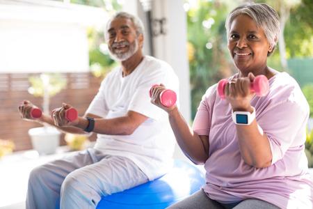 Photo pour Portrait of senior couple lifting dumbbells exercising in yar - image libre de droit
