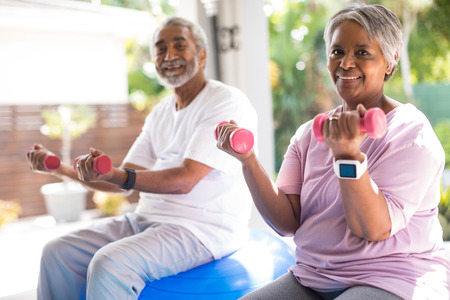 Foto de Portrait of senior couple lifting dumbbells exercising in yar - Imagen libre de derechos