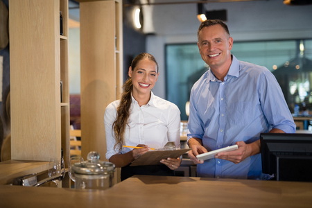 Portrait of smiling manager and bartender standing at bar counter