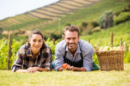Photo pour Portrait of smiling young couple lying down at vineyard - image libre de droit