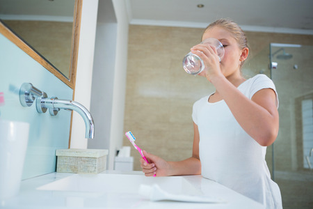 Photo pour Girl drinking water while holding toothbrush by sink in bathroom - image libre de droit