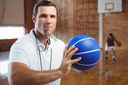 Foto de Portrait of coach whistling while holding basketball in court - Imagen libre de derechos