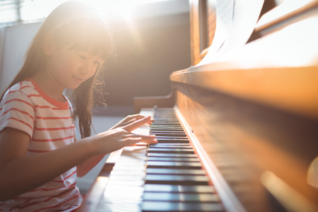 Photo for Smiling girl practicing piano in classroom at music school - Royalty Free Image