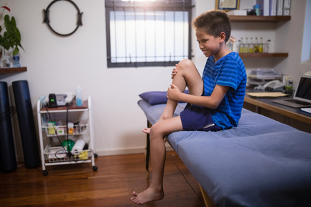 Photo for Boy frowning with knee pain while sitting on bed at hospital ward - Royalty Free Image