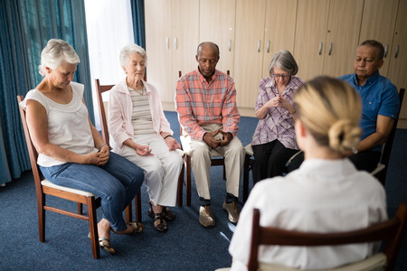 Photo pour Senior people meditating with female doctor at retirement home - image libre de droit