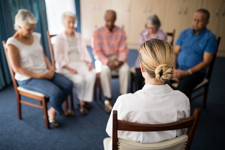 Photo pour Rear view of female doctor meditating with senior people at retirement home - image libre de droit