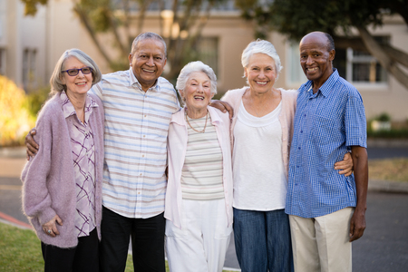 Photo pour Portrait of cheerful senior people standing with arms around outside nursing home - image libre de droit