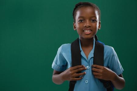 Foto de Smiling school girl with backpack standing against chalk board - Imagen libre de derechos