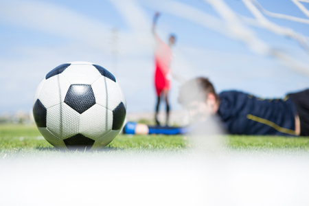 Goalkeeper lying on field while playing soccer against sky