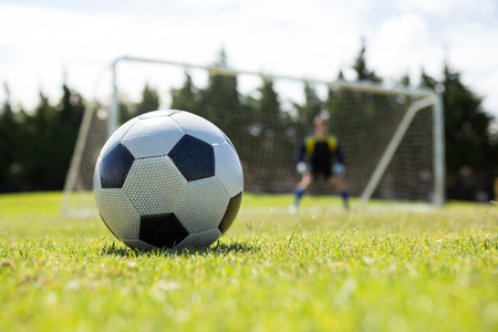 Close up of soccer ball on field against goalkeeper