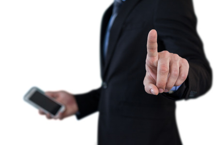 Mid section of businessman holding smartphone while using invisible interface against white background