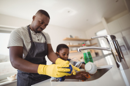 Photo for Father and son cleaning utensils in kitchen at home - Royalty Free Image