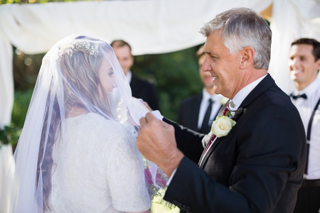 Photo pour Happy father removing veil of his daughter during wedding - image libre de droit