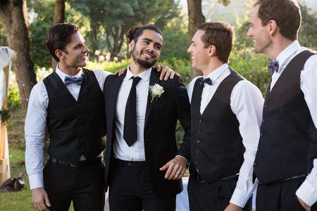 Foto de Happy groom and groomsmen having fun in park - Imagen libre de derechos
