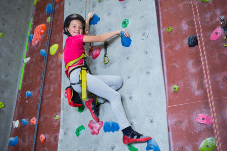 Photo for Portrait of confident teenage girl practicing rock climbing in fitness studio - Royalty Free Image