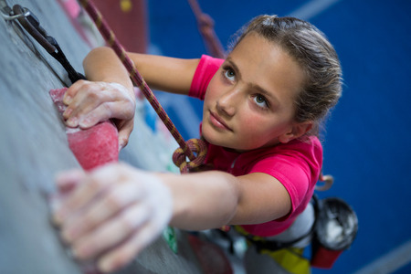 Photo for Determined teenage girl practicing rock climbing in fitness studio - Royalty Free Image