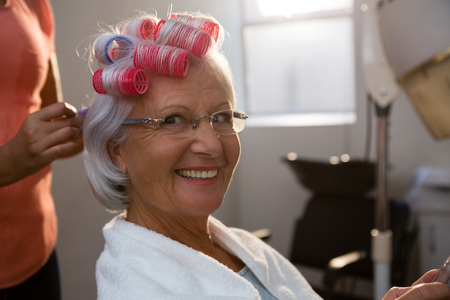 Photo for Cropped hands of hairstylist removing curlers from smiling senior woman hair - Royalty Free Image