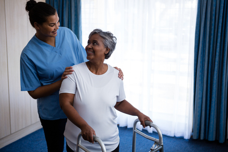 Foto de Smiling nurse assisting senior woman in walking with walker at nursing home - Imagen libre de derechos