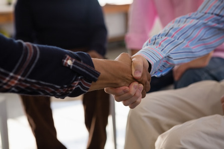 Photo for Close up of friends doing handshake while sitting in art class - Royalty Free Image