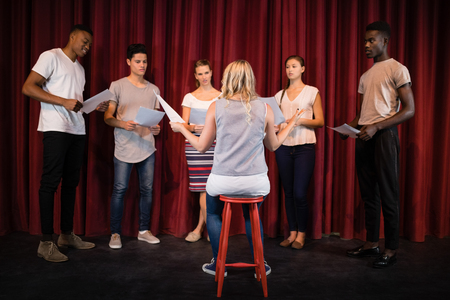 Photo for Actors reading their scripts on stage in theatre - Royalty Free Image