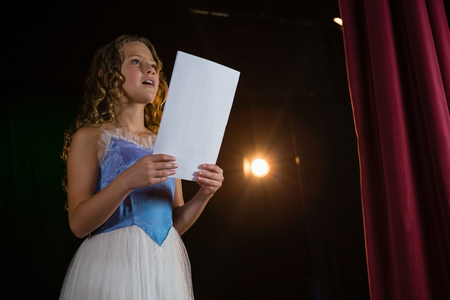 Photo for Female artist reading her scripts on stage in theatre - Royalty Free Image