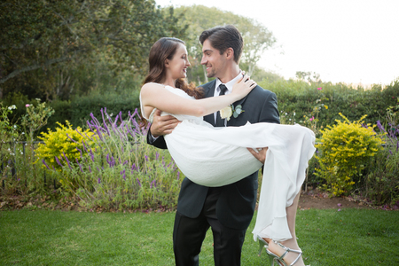 Photo for Happy bridegroom carrying bride while walking in park - Royalty Free Image