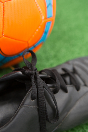 Close-up of football and cleats on artificial grass