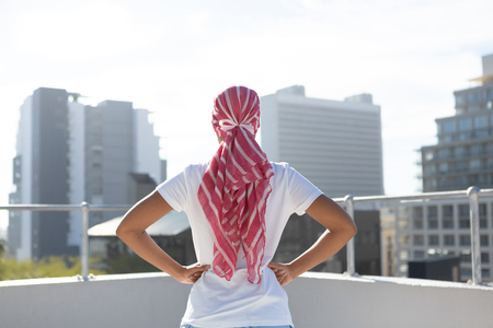 Photo pour Confident woman standing in city for breast cancer awareness against urban background - image libre de droit