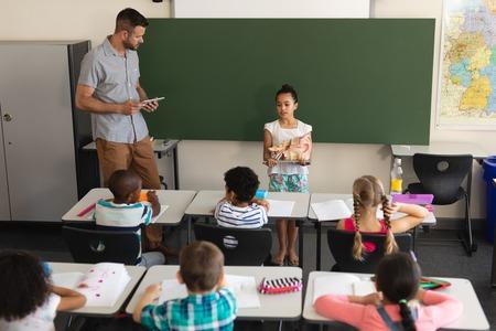 Foto de High angle view of schoolgirl explaining anatomical model in classroom of elementary school - Imagen libre de derechos