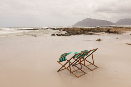 Foto de Side view of empty sun lounger chairs at the beach with mountains and ocean in the background - Imagen libre de derechos