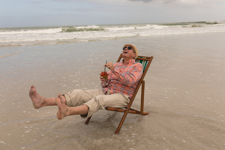 Foto de Side view of active senior man having cocktail drink while relaxing in a sun lounger at the beach with ocean in the background. He wears a hat - Imagen libre de derechos