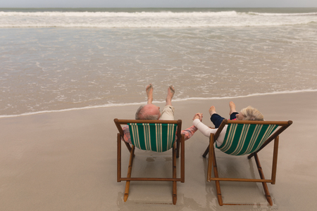 Foto de High angle view of senior couple holding hands of each other on the beach - Imagen libre de derechos
