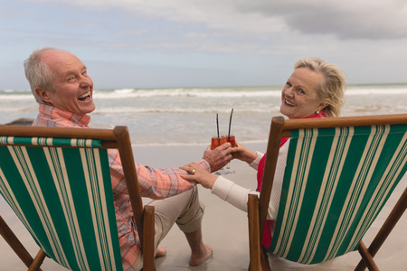 Foto de Back view of active senior couple toasting glasses of cocktail drinks in a sun lounger at the beach with ocean in the background. They seem happy - Imagen libre de derechos