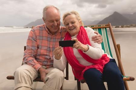 Foto de Active senior couple using mobile phone while relaxing in a sun lounger on the beach - Imagen libre de derechos