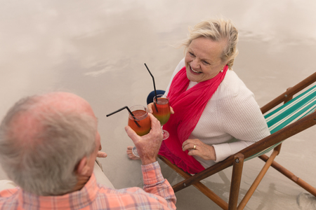 Foto de High view of active senior couple toasting glasses of cocktail drinks in a sun lounger at the beach. They seem happy - Imagen libre de derechos