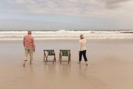 Foto de Back view of active senior couple walking at the beach with ocean in the background - Imagen libre de derechos