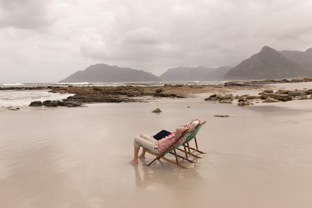 Foto de Side view of active senior couple relaxing with hands behind head in a sun lounger on the beach - Imagen libre de derechos