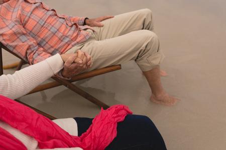 Foto de High angle view of oh active senior couple holding hands of each other on the beach - Imagen libre de derechos