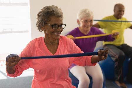 Foto de Happy senior woman exercising with resistance band in fitness studio - Imagen libre de derechos