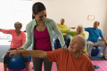 Photo pour Front view of happy young female trainer assisting senior man in fitness studio - image libre de droit