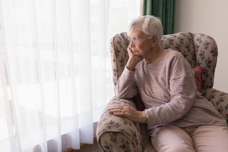 Photo for Front view of thoughting senior woman sitting on the couch and looking outside through window at home - Royalty Free Image