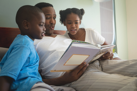 Photo pour Side view of African American father with his children reading storybook on bed in bedroom at home - image libre de droit