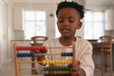 Foto de Front view of cute African American boy learning mathematics with abacus in a comfortable home - Imagen libre de derechos